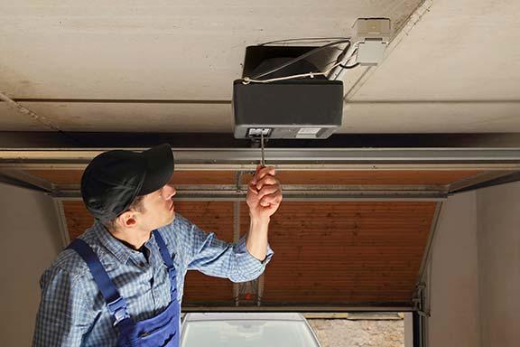 Garage door contractor repairing a garage door opener